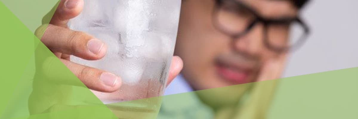 man_with_sensitive_teeth_and_holding_glass_of_cold_water_with_ice.jpeg
